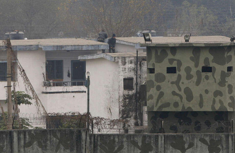 Indian soldiers are seen on a rooftop at an airbase in Pathankot, India, Monday, Jan. 4, 2016. After saying all the gunmen who attacked the Indian airbase near the Pakistan border were dead, Indian officials said at least two attackers remained and vowed to kill them Monday to end a more than 48-hour siege. (AP Photo/Channi Anand)