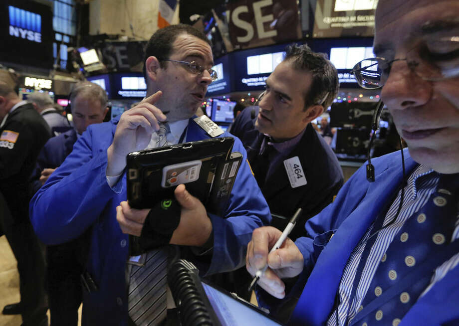Traders Richard Scardino, left, and Gregory Rowe, center, confer on the floor of the New York Stock Exchange Monday, Jan. 5, 2015. US stocks opened lower Monday, led by declines in energy stocks as the price of oil plunged again. (AP Photo/Richard Drew)