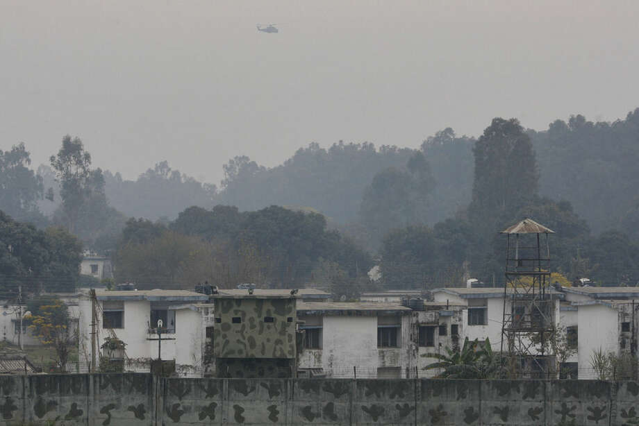 An Indian military helicopter keeps watch on the situation as Indian soldiers take position on a rooftop at an airbase in Pathankot, India, Monday, Jan. 4, 2016. After saying all the gunmen who attacked the Indian airbase near the Pakistan border were dead, Indian officials said at least two attackers remained and vowed to kill them Monday to end a more than 48-hour siege. (AP Photo/Channi Anand)