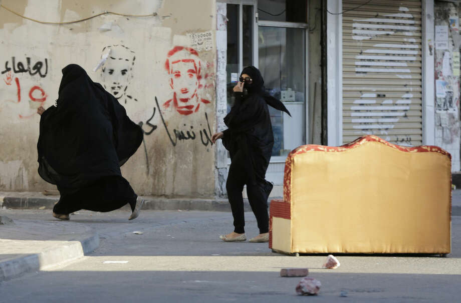 "Bahraini women run from approaching riot police who were chasing protesters against Saudi Arabia's execution of Shiite cleric Sheikh Nimr al-Nimr in Daih, Bahrain, a largely Shiite suburb of the capital, Monday, Jan. 4, 2016. Graffiti on the wall reads, ""we will not forget you,"" beneath pictures of people killed in previous unrest. Allies of Saudi Arabia, including the monarchy in neighboring Bahrain, began scaling down their diplomatic ties to Iran in the wake of the ransacking of Saudi diplomatic missions in Iran that followed al-Nimr's execution. (AP Photo/Hasan Jamali)"