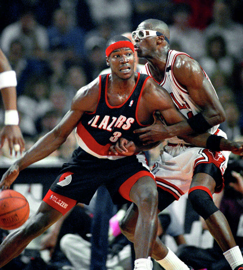 FILE - In this June 4, 1992, file photo, Portland Trail Blazers' Cliff Robinson drives on Chicago Bulls' Horace Grant during Game 1 of the NBA Finals in Chicago. Dennis Rodman has named a team of former NBA players to participate in an exhibition basketball game in Pyongyang, North Korea. Rodman leads a team that includes former NBA All-Stars Kenny Anderson, Robinson, and Vin Baker. Craig Hodges, Doug Christie and Charles D. Smith are on the team, as well. They will play against a top North Korean Senior National team on Jan. 8, marking Kim Jong Un's birthday. (AP Photo/John Swart, File) / AP