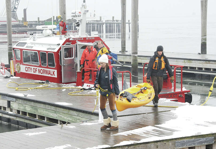 Norwalk emergency crew brings back a couple who were on a kayak in Norwalk harbor Sunday morning. The call came in around 11:00 am saying they were stuck in ice. Hour photo/Matthew Vinci