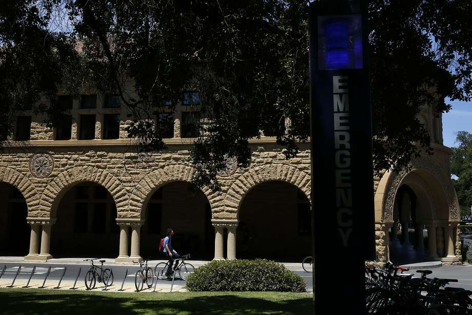 An emergency campus phone is seen in the foreground as a student rides past Pigott Hall on the campus of Stanford University June 9, 2016 in Stanford, Calif. Photo: Leah Millis, The Chronicle