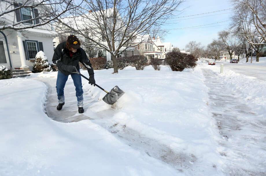 Arnold King shovels his walkway Tuesday, Jan. 6, 2015, along Mt. Pleasant Street in Dubuque, Iowa. A winter storm system moved through the Midwest which brought snow and cold temperatures to parts of Nebraska and Iowa. (AP Photo/Telegraph Herald, Jessica Reilly)