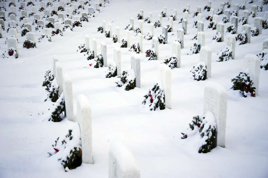 Snow covers wreaths and tombstones at Arlington National Cemetery in Arlington, Va., Tuesday, Jan. 6, 2015, after a snow storm his the Washington area. (AP Photo/Manuel Balce Ceneta)