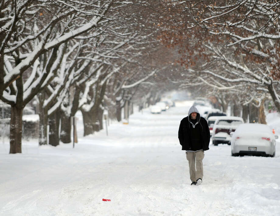 Jeff Armstrong, of Rock Island, Ill., walks up 15th Street in Moline, Ill., en route to work at the BelGrade restaurant Tuesday, Jan. 6, 2015. The Quad-Cities area woke up to 5 to 6 inches of fresh snow slowing the morning commute by car or foot. (AP Photo/The Dispatch, Todd Mizener) QUAD CITY TIMES OUT; MANDATORY CREDIT