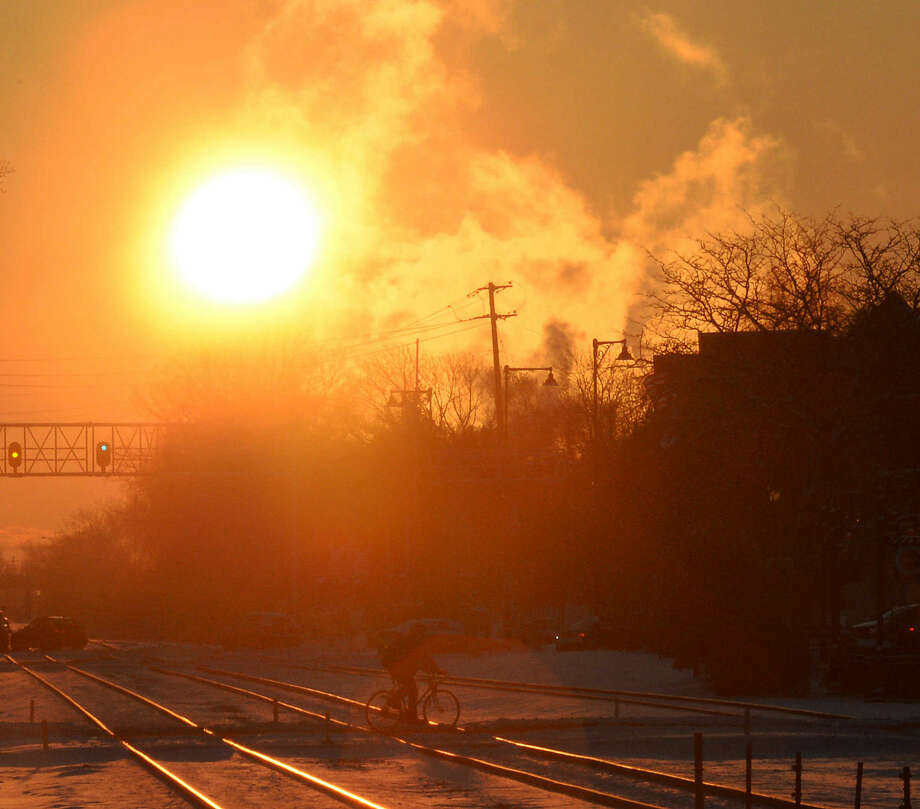 The early morning sun rises over Palatine, Ill. as snow impacted the suburbs of Chicago on Tuesday, Jan. 6, 2015. Below-zero temperatures are expected to follow on Wednesday. (AP Photo/Daily Herald, Mark Welsh)