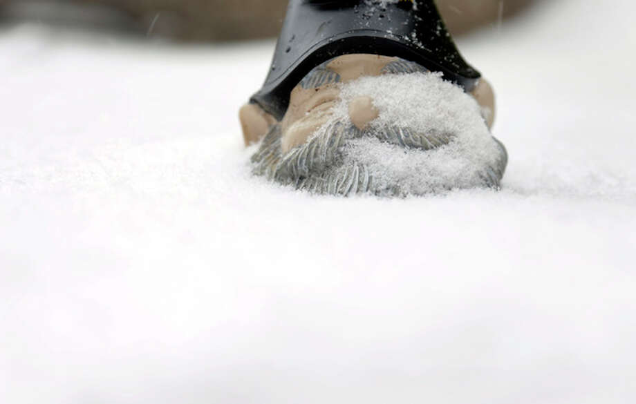 A garden gnome sits up to its chin in snow Sunday, Jan. 5, 2014, in St. Louis. Snow that began in parts of Missouri Saturday night picked up intensity after dawn Sunday with several inches of snow on the ground by midmorning and more on the way. (AP Photo/Jeff Roberson) / AP