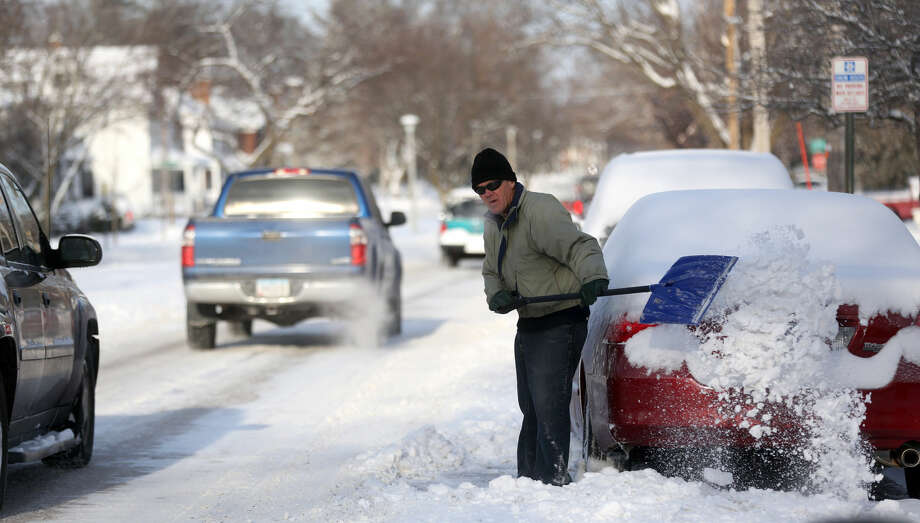 A man clears snowalong South Grandview Avenue in Dubuque, Iowa on Tuesday, Jan. 6, 2015. A winter storm system moved through the Midwest which brought snow and cold temperatures to parts of Nebraska and Iowa. (AP Photo/Telegraph Herald, Jessica Reilly)