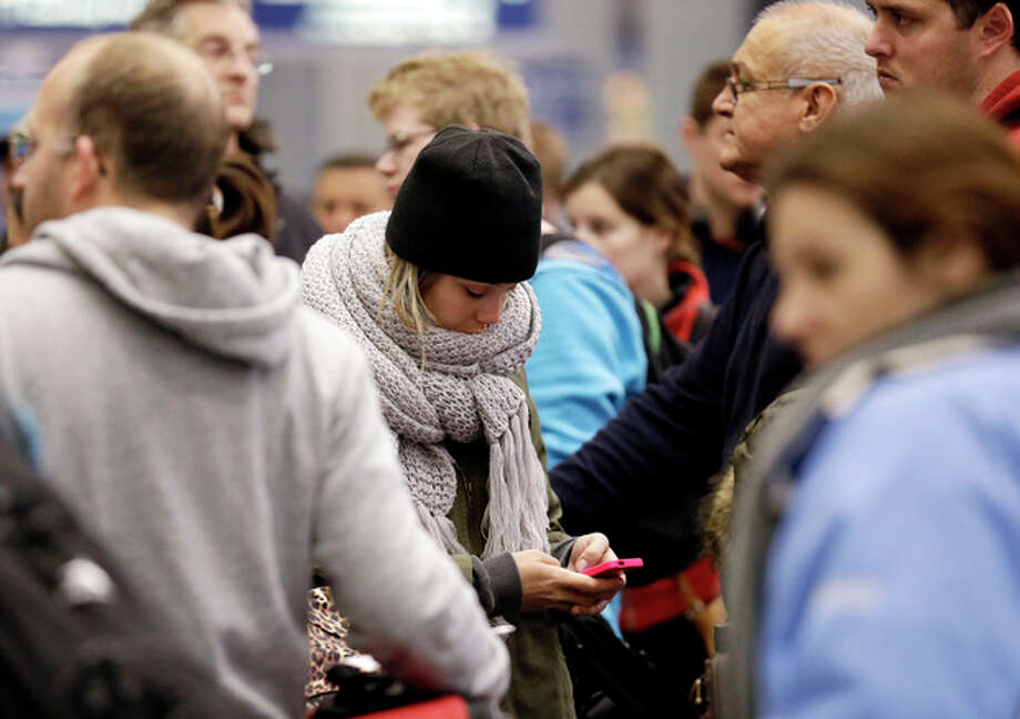 A woman checks her cell phone as she waits at the check-in line in Terminal 3 at O'Hare International Airport in Chicago on Sunday, Jan. 5, 2014. Illinois residents are digging out of more snow and preparing for bitterly cold temperatures. Sunday night temperatures are predicted to drop drastically, to about minus 20 degrees. (AP Photo/Nam Y. Huh) / AP