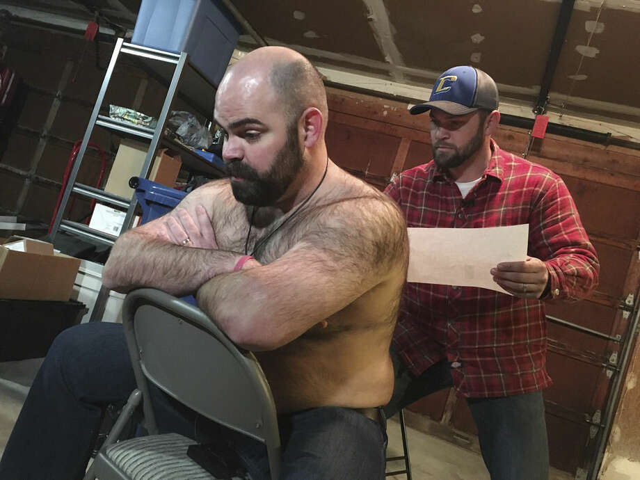 In this Dec. 29, 2015 photo provided by KTVB-TV, Tyler Harding, right, trims a design on Mike Wolfe out of his back hair in Nampa, Idaho. Wolfe and Harding meet up several times throughout the year to design a new creation on Wolfe's back. The designs have since been compiled for a calendar. (Brian Holmes/KTVB-TV via AP)
