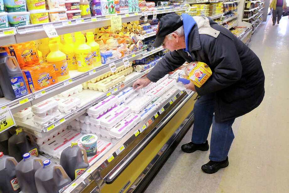 Jack Craig checks a carton of eggs as he picks up a few items at the Harvest Supermarket on Eighth Street in Anderson Ind. on Saturday, Jan. 4, 2014. Grocery and hardware stores were busy as people prepared for the winter storm forecast to arrive on Sunday. (AP Photo/The Herald Bulletin, Don Knight) / The Herald Bulletin