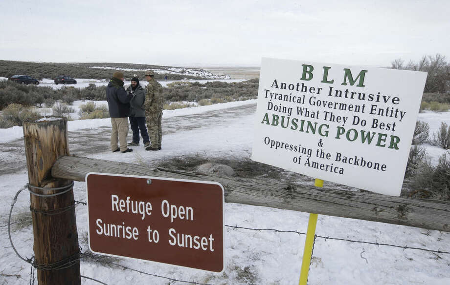 """Members of the group occupying the Malheur National Wildlife Refuge headquarters stand guard Monday, Jan. 4, 2016, near Burns, Ore. The group calls itself Citizens for Constitutional Freedom and has sent a """"demand for redress"""" to local, state and federal officials. The armed anti-government group took over the remote national wildlife refuge in Oregon as part of a decades-long fight over public lands in the West. (AP Photo/Rick Bowmer)"""