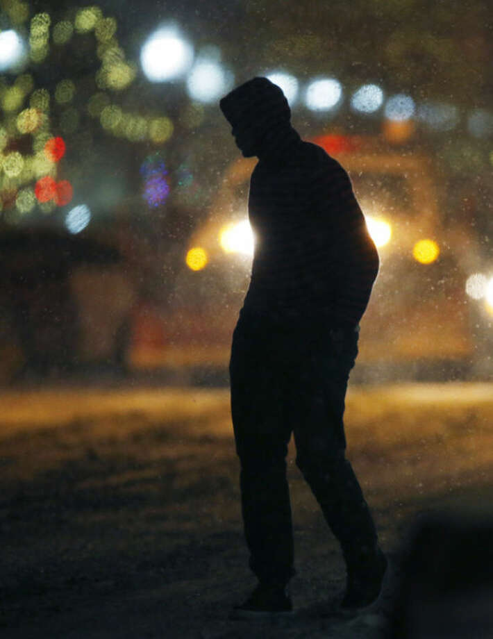 A pedestrian walks along Massachusetts Street as snow falls in Lawrence, Kan., Sunday, Jan. 5, 2014. The area is under a winter weather advisory and wind chill warnings. (AP Photo/Orlin Wagner)