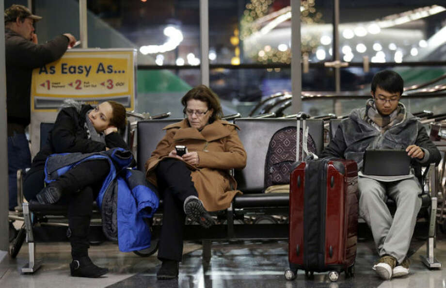 Travelers deal with long waits and flight cancellations at O'Hare International Airport in Chicago on Sunday, Jan. 5, 2014. Temperatures not seen in years are likely to set records in the coming days across the Midwest, Northeast and South, creating dangerous travel conditions and prompting church and school closures. (AP Photo/Nam Y. Huh)