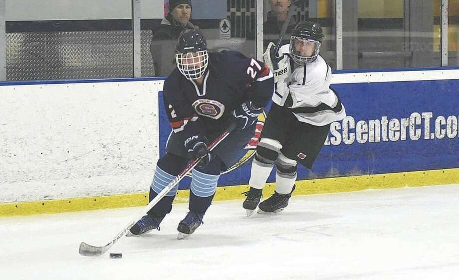 Hour photo/John NashStamford-Westhill-Staples skater Erin McGroarty skates up ice in front of an Amity-Cheshire-North Haven player during Monday's game at The Rinks in Shelton.