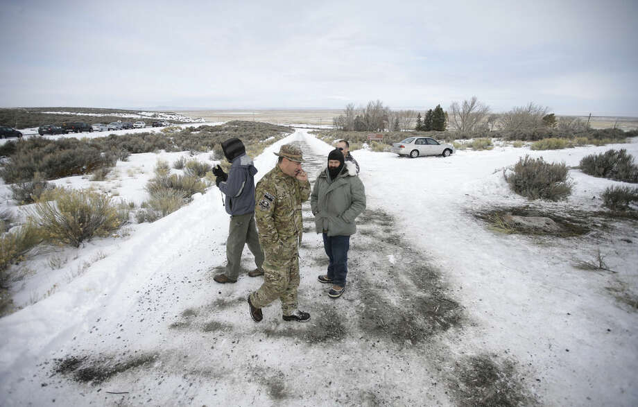 "Members of the group occupying the Malheur National Wildlife Refuge headquarters stand guard along a roadside Monday, Jan. 4, 2016, near Burns, Ore. The group calls itself Citizens for Constitutional Freedom and has sent a ""demand for redress"" to local, state and federal officials. (AP Photo/Rick Bowmer)"