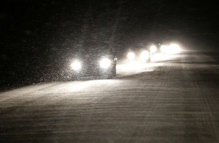 Motorists make there way west as snow begins to build up on US 24 near Belvue, Kan., Saturday, Jan. 4, 2014. The area is under a winter weather advisory and wind chill warning. (AP Photo/Orlin Wagner) / AP