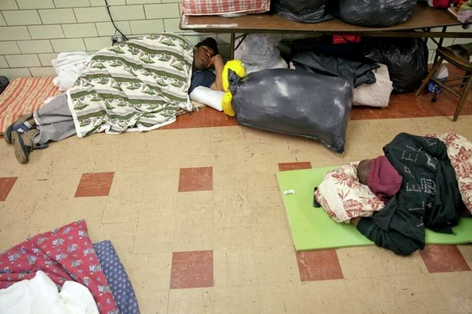 People sleep on the floor at a Catholic Charities warming center on Saturday, Jan. 4, 2014, in Flint, Mich. A deep freeze is expected to arrive over the Midwest Sunday with potential record-low temperatures, heightening fears of frostbite and hypothermia. (AP Photo/The Flint Journal, Michelle Tessier) / The Flint Journal