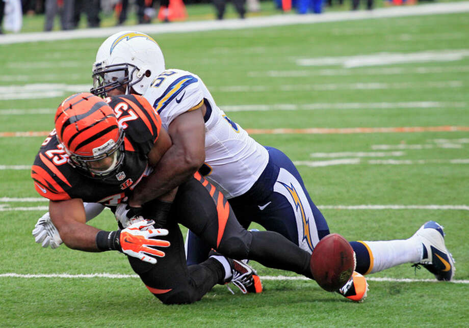 Cincinnati Bengals running back Giovani Bernard (25) fumbles as he is hit by San Diego Chargers linebacker Donald Butler in the first half of an NFL wild-card playoff football game on Sunday, Jan. 5, 2014, in Cincinnati. (AP Photo/Tom Uhlman) / FR31154 AP