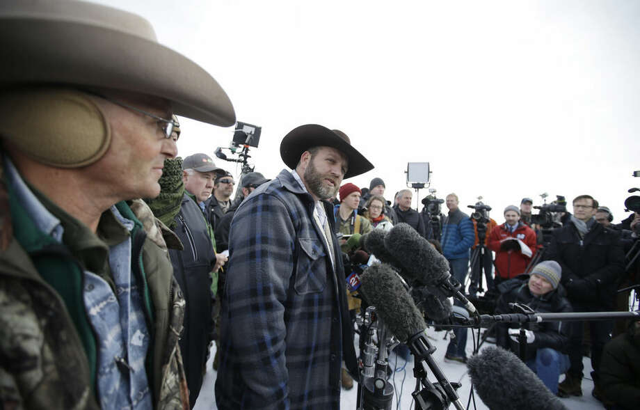 Ammon Bundy, center, one of the sons of Nevada rancher Cliven Bundy, speaks with reporters during a news conference at Malheur National Wildlife Refuge headquarters Monday, Jan. 4, 2016, near Burns, Ore. Bundy, who was involved in a 2014 standoff with the government over grazing rights, told reporters on Monday that two local ranchers who face long prison sentences for setting fire to land have been treated unfairly. (AP Photo/Rick Bowmer)