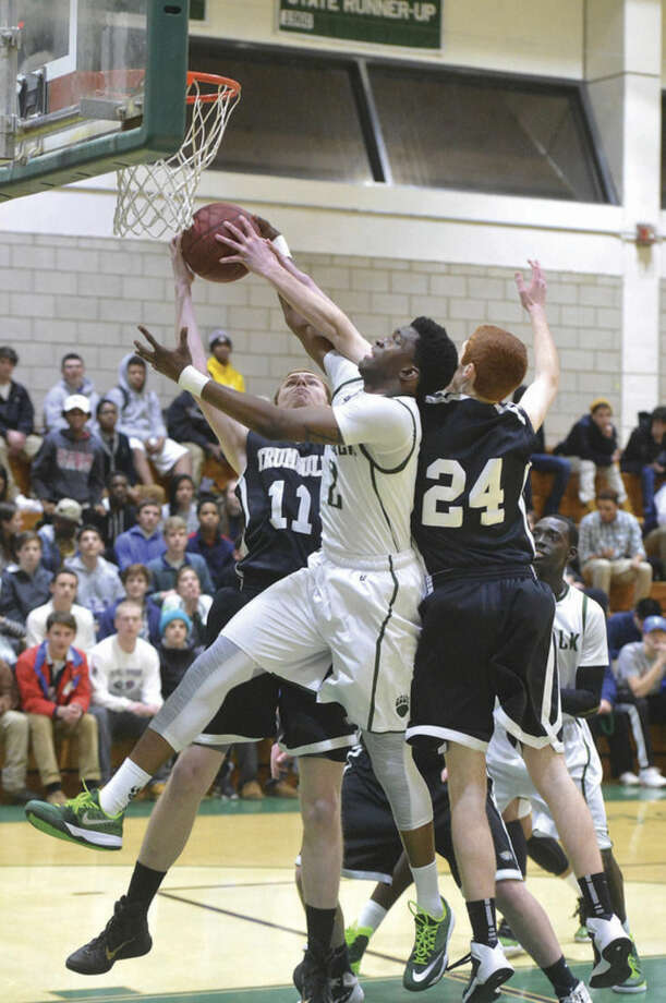 Hour photo/Alex von KleydorffNorwalk's Zaire Wilson (2) grabs a rebound during Tuesday night's game against Trumbull.
