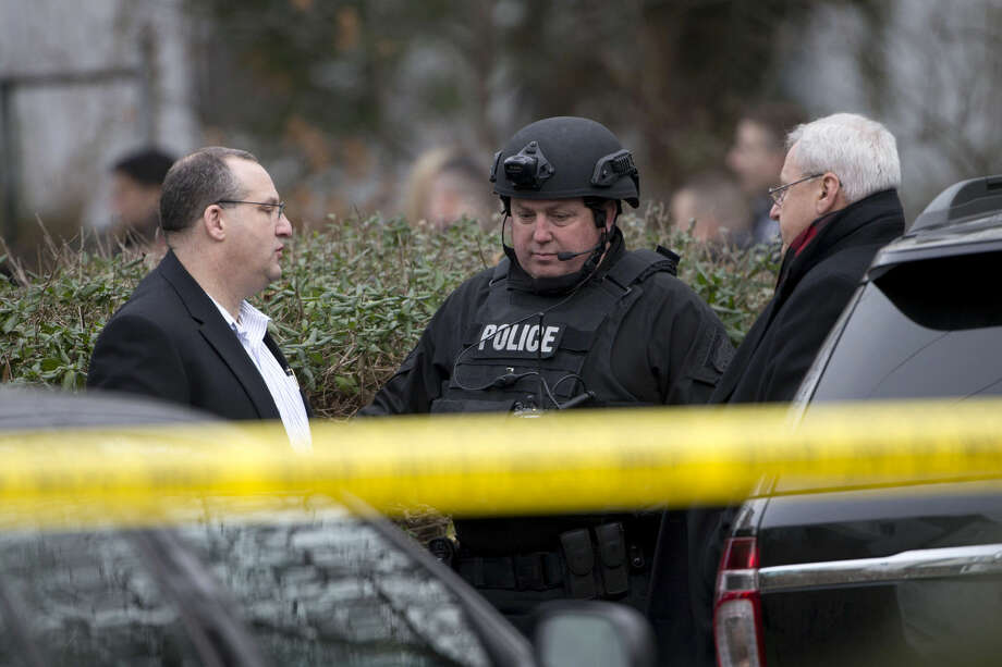 Law enforcement standby as investigators work the scene at one of the residences where suspect Edward Archer has lived Friday, Jan. 8, 2016, in Yeadon, Pa. Archer accused of ambushing a police officer and firing shots at point-blank range said he was acting in the name of Islam and had pledged allegiance to the Islamic State group, Philadelphia authorities said Friday. (AP Photo/Matt Rourke)