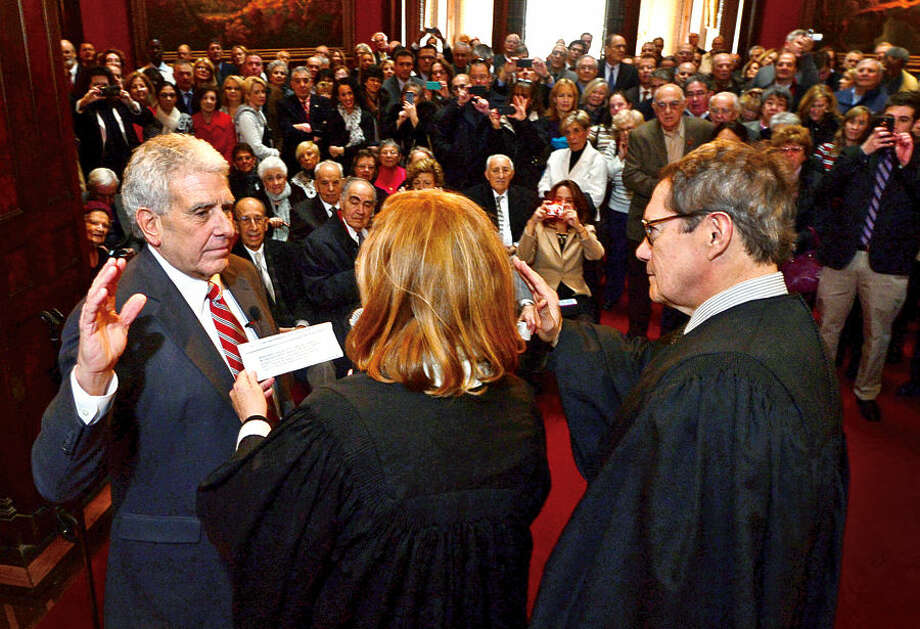 Hour photo / Erik Trautmann Norwalk Judge of Probate Anthony DePanfilis gets sworn in for his last 4 year term by Superior Court Judges Eddie Rodriguez and Maureen Dennis during a ceremony at Lockwood Mathews Mansion Wednesday morning.