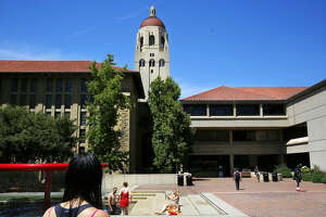 People play in the Red Hoop Fountain as others lounge in the sun outside of the Cecil H Green Library on the campus of Stanford University June 9, 2016 in Stanford, Calif.