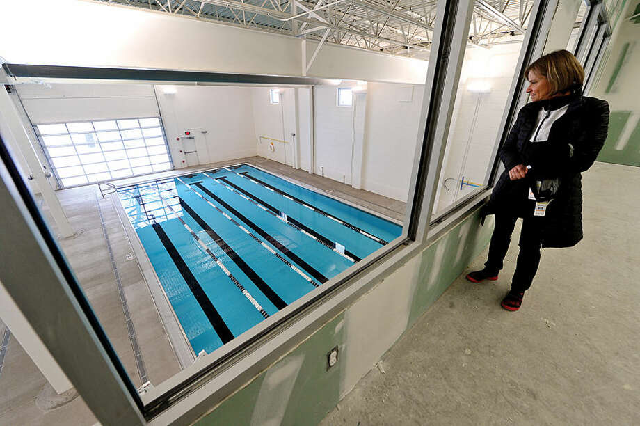 Hour photo / Erik Trautmann The Swim Seventy Aquacenter's triathalon director, Pascale Butcher, looks out of the yoga studio at the 30×60 warm water lesson and fitness pool. The Center also features ia a 27,000 sqaure foot facilty with a 6 lane, 50 meter lap pool, an endless pool for stroke analysis and therapy, a dedicated triathlon training center and yoga studio.