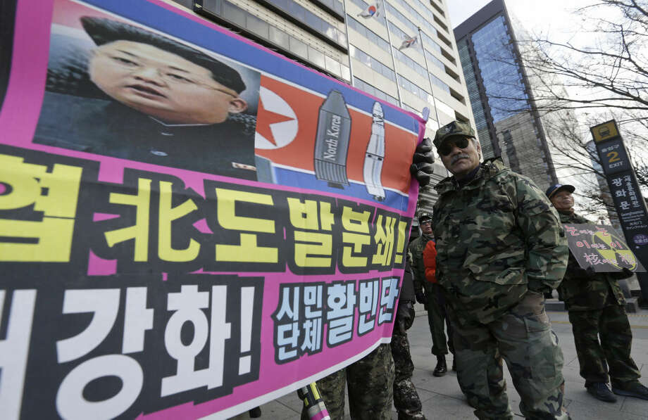 "A banner shows a picture of North Korean leader Kim Jong Un as South Korean war veterans stage a rally against North Korea in Seoul, South Korea, Saturday, Jan. 9, 2016. North Korea trumpets a hydrogen bomb test. South Korea responds by cranking up blasts of harsh propaganda from giant green speakers aimed across the world's most dangerous border. The letters at a banner read ""Smash the North Korean provocation which threatens peace of global village!"" (AP Photo/Ahn Young-joon)"