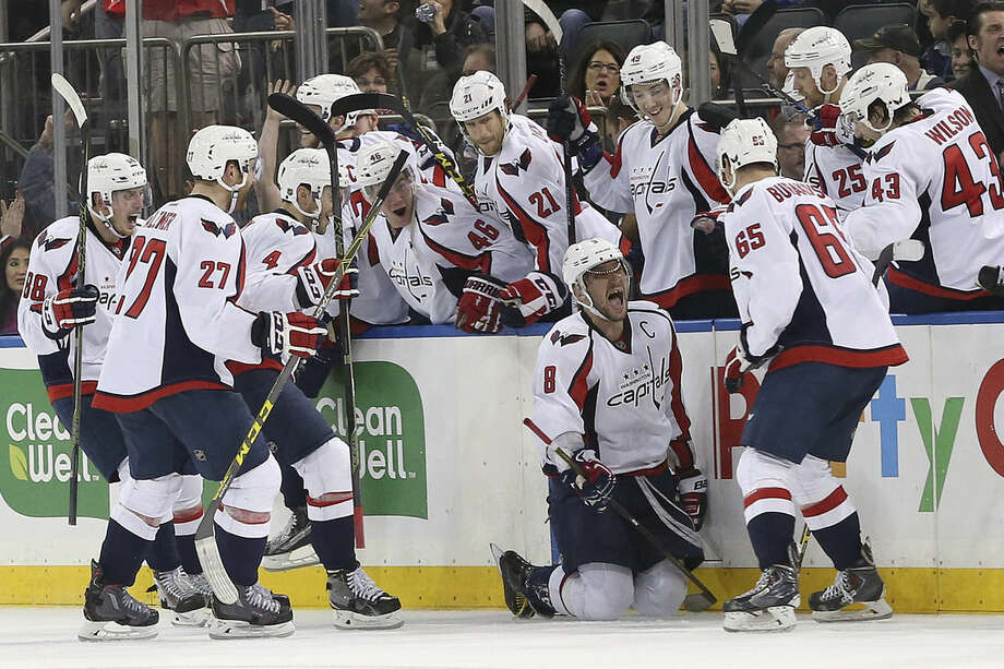 Washington Capitals left wing Alex Ovechkin (8) celebrates with his teammates after scoring the game-winning goal during overtime of an NHL hockey game against the New York Rangers, Saturday, Jan. 9, 2016, at Madison Square Garden in New York. The Capitals won 4-3. (AP Photo/Mary Altaffer)