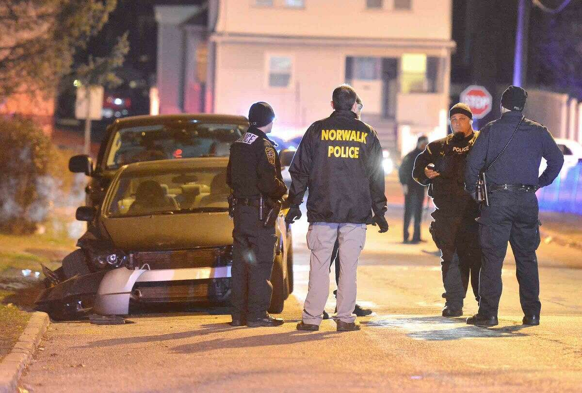 Hour Photo/Alex von Kleydorff Norwalk Police investigate an area and a damaged vehicle on Sheridan St Friday night possibly connected to a shooting in the area