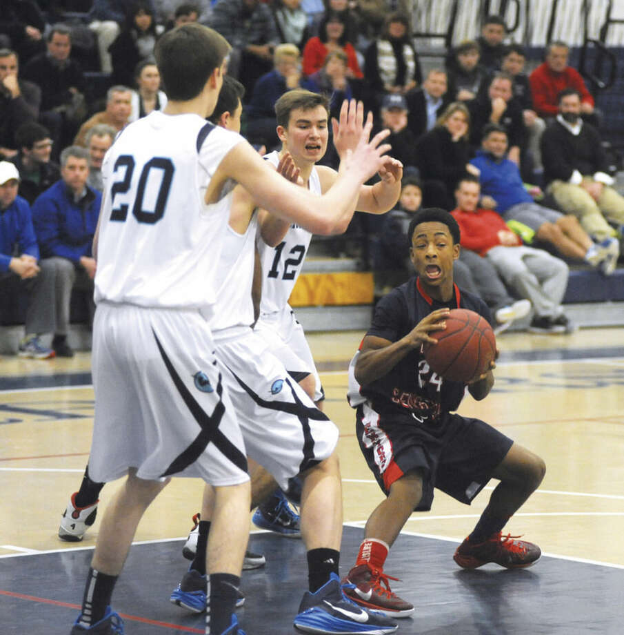 Hour photo/John NashBrien McMahon's Eric Day, right, finds himself trapped in the paint by a trio of Wilton defenders, including Richie Williams (12) and Michael Bingaman (20) during Tuesday's FCIAC boys basketball game in Wilton.