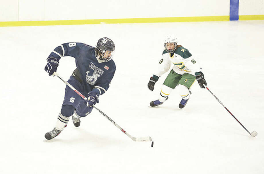 Hour photo/Danielle CallowayStaples-Weston-Shelton's Matthew Bidgood, left, and Trinity Catholic's Martin Hakanson go for the puck during a game at Terry Conners Rink in Stamford Saturday evening. The Staples co-op defeated Trinity Catholic 6-1 to raise its record to 5-2 overall.