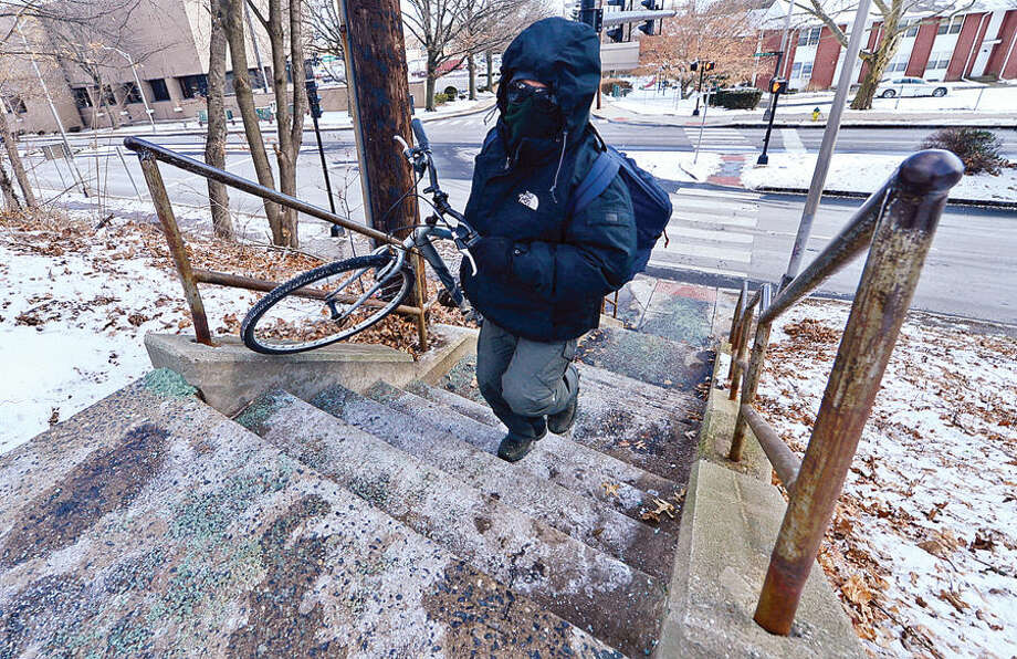 Hour photo / Erik Trautmann Norwalk resident Jimmy Chaguay takes his bicycle up the stairs connecting Martin Luther King Jr. Boulevard and Clay St. Wednesday. The Norwalk Common Council's Public Works Committee tables an action on approving use of $250,000 of state money to heat and light staircase from Dr. Martin Luther King Jr. Drive to Clay Street.