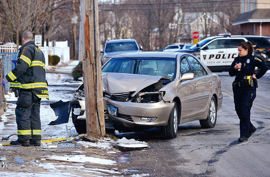 Hour photo / Erik Trautmann Norwalk fire and police personnel respond to a single car accident where a woman crashed her Lexus into a utility pole at the corner of Academy and Chapel closing those streets to through traffic until the damaged pole is repaired.