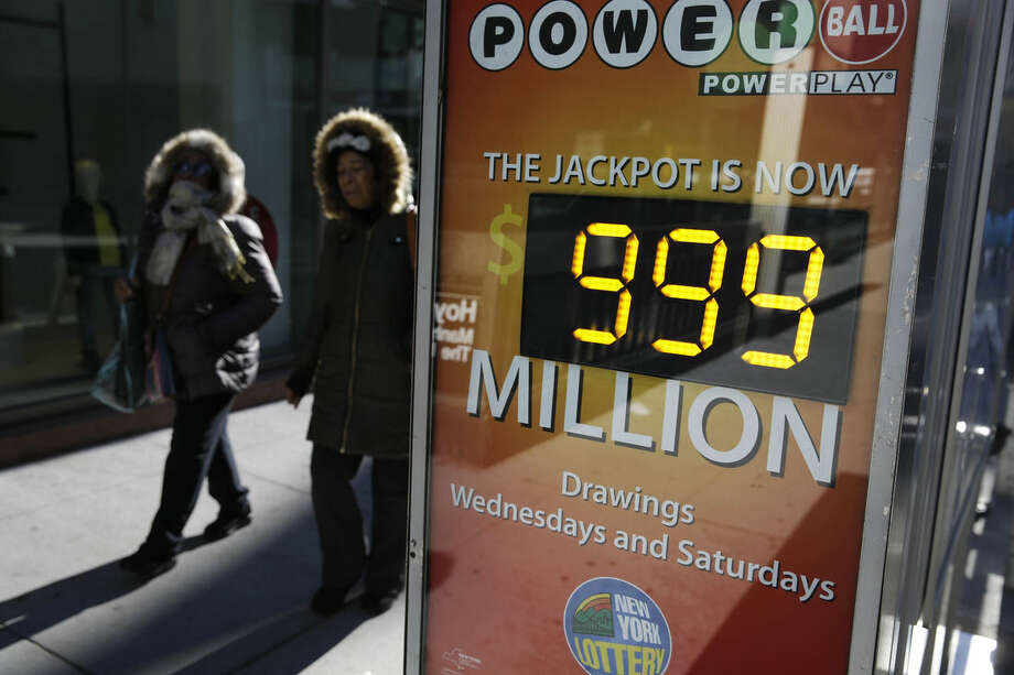 People walk past a sign advertising the Powerball lottery in New York, Monday, Jan. 11, 2016. The jackpot is so big that billboards around the country have to advertise the prize as $999 million because they're not built to show billions. (AP Photo/Seth Wenig)