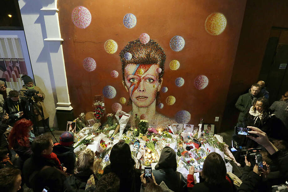 People gather next to tributes placed near a mural of British singer David Bowie by artist Jimmy C, in Brixton, south London, Monday, Jan. 11, 2016. Bowie, the other-worldly musician who broke pop and rock boundaries with his creative musicianship, nonconformity, striking visuals and a genre-spanning persona he christened Ziggy Stardust, died of cancer Sunday aged 69. He was born in Brixton. (AP Photo/Tim Ireland)