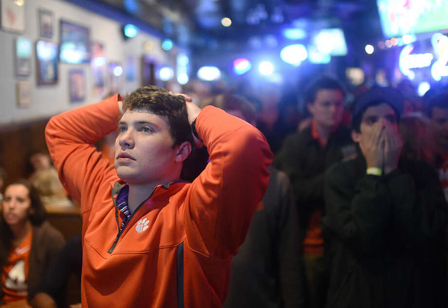 Clemson fan Trey Funderburke reacts to an Alabama touchdown in the NCAA college football playoff championship game at Tiger Town Tavern on Monday, Jan. 11, 2016, in Clemson, S.C. (AP Photo/Rainier Ehrhardt)