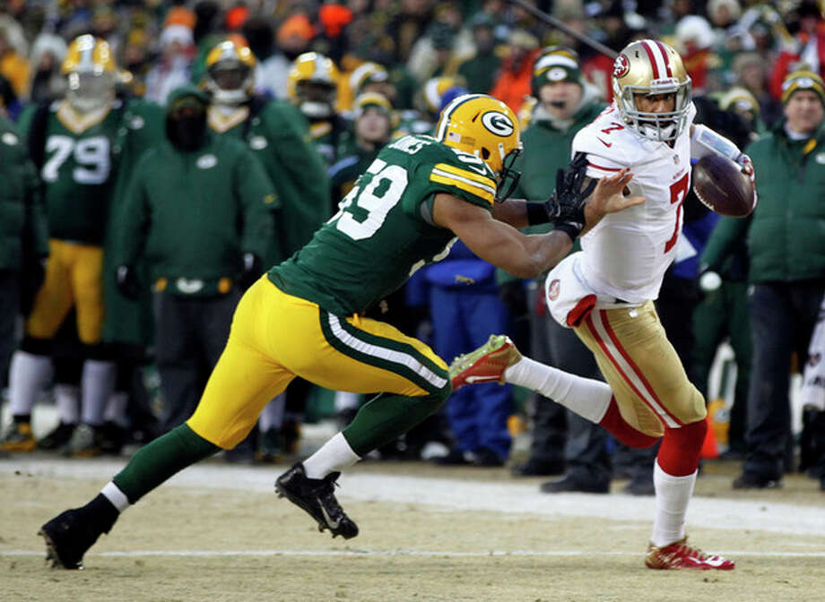 San Francisco 49ers quarterback Colin Kaepernick (7) runs against Green Bay Packers inside linebacker Brad Jones (59) during the first half of an NFL wild-card playoff football game, Sunday, Jan. 5, 2014, in Green Bay, Wis. (AP Photo/Mike Roemer) / FR155603 AP