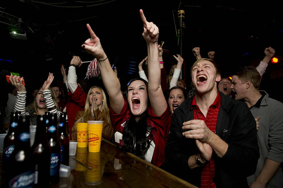 Alabama fan Alanna Jackson, of Foxboro, Mass., cheers after Alabama defeated Clemson 45-40 in the NCAA college playoff championship football game at Gallettes Bar, Monday, Jan. 11, 2016, in Tuscaloosa, Ala. (AP Photo/Brynn Anderson)