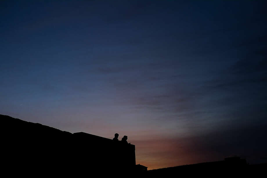Two people stand over an ancient wall as the sun sets during a mild winter day, in Pamplona, northern Spain, Monday, Jan. 11, 2016. (AP Photo/Alvaro Barrientos)