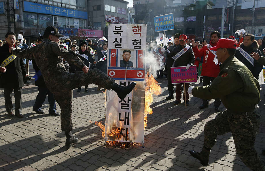 "A member of a South Korean conservative group kicks a burning banner with image of North Korean leader Kim Jong Un and North Korean flags during a rally denouncing the North, in Paju, South Korea, Monday, Jan. 11, 2016. Kim looked Monday to milk his country's recent nuclear test as a propaganda victory, praising his scientists and vowing more nuclear bombs a day after the U.S. flew a powerful nuclear-capable warplane close to the North in a show of force. The banner reads: ""Smash North Korean nuclear test."" (AP Photo/Lee Jin-man)"