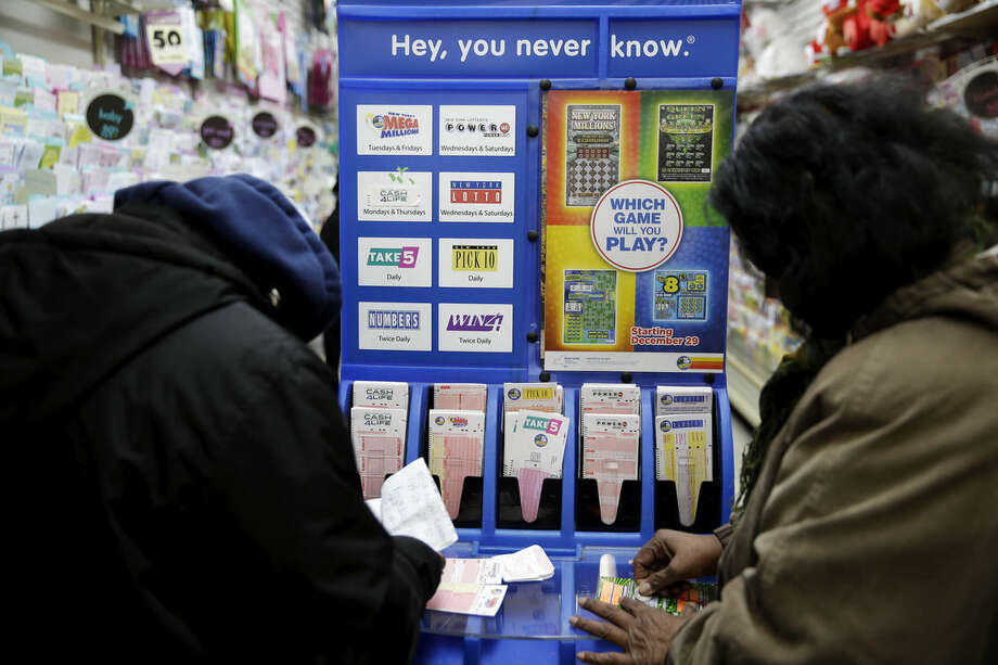 People play various lottery games at a store in New York, Monday, Jan. 11, 2016. Lottery officials say the Powerball jackpot has grown to more than a billion dollars. (AP Photo/Seth Wenig)