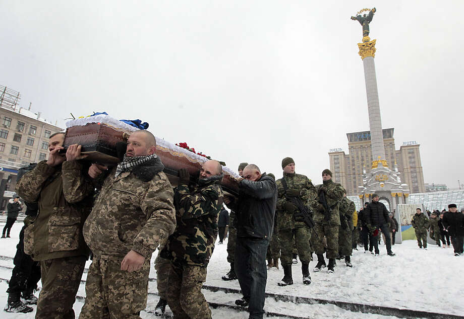 Ukrainian soldiers carry the coffin bearing the body of police captain Oleksandr IlnItsky, who was shot dead by a pro-Russian sniper in the war conflict-hit Donetsk region, during a commemoration ceremony in Independence Square in Kiev, Ukraine, on Monday, Jan. 11, 2016. IlnItsky was killed on Jan. 9 as he was rescuing civilian residents from the fire by pro-Russian separatists. (AP Photo/Efrem Lukatsky)