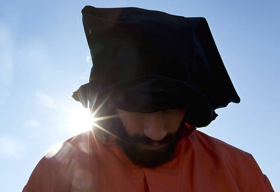 A protester wearing an orange jumpsuit depicting a Guantanamo Bay detainee, participates in a rally outside of the White House in Washington Monday, Jan. 11, 2016, calling for a close of the detention center at the U.S. base at Guantanamo Bay, Cuba. (AP Photo/Carolyn Kaster)