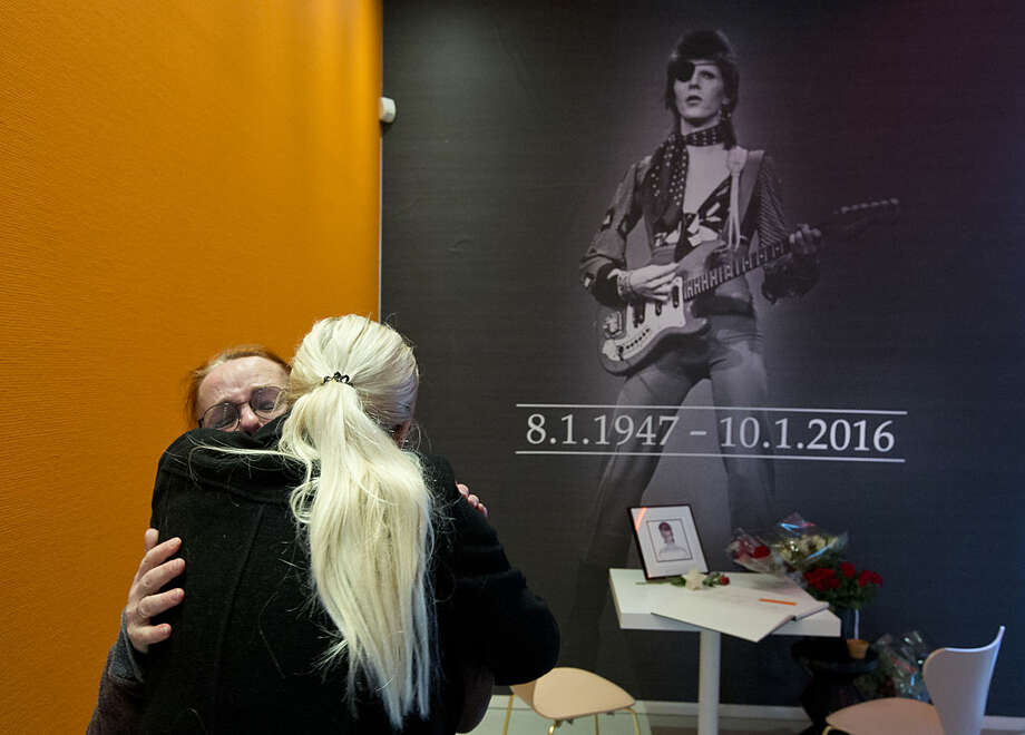 "A crying woman, left, is comforted after signing a book of condolences for deceased popstar David Bowie at the Groninger Museum which hosts the ""DAVID BOWIE is' exhibit, in Groningen, northern Netherlands, Monday, Jan. 11, 2016. The museum is normally closed on Mondays but opened its doors to allow people to sign a condolence register and visit the Bowie exhibit which runs till March 13, 2016. (AP Photo/Peter Dejong)"