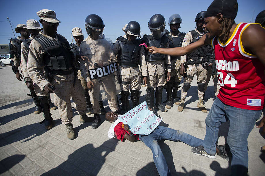 "A demonstrator lies on the ground in front of the national police officers during a protest against the installation of the Haitian parliament in Port-au-Prince, Haiti, Monday, Jan. 11, 2016. The demonstrators are claiming that the law makers are tainted because of the fraud they believed occurred during the first round of elections. This time around, second place presidential finisher Jude Celestin rejected the first-round results as a ""ridiculous farce"" and his Group of Eight opposition alliance is calling for a transitional government to organize a ""fair"" election. (AP Photo/Dieu Nalio Chery)"