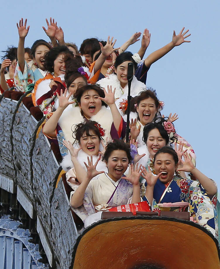 Kimono-clad women, who reach the age of 20 this year, ride a roller coaster following their Coming of Age ceremony at Toshimaen amusement park on the national holiday in Tokyo, Monday, Jan. 11, 2016. (AP Photo/Shizuo Kambayashi)